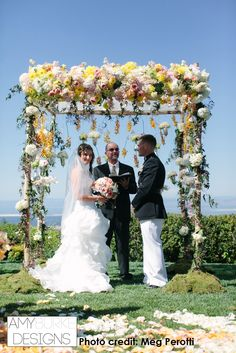 Beautiful rustic inspired chuppah. Yellow, pink and green color scheme with a beautiful blue sky in the background. @megperotti #rustic Location Thomas Fogarty Winery