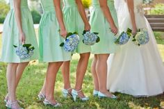 Bridesmaids in mint dresses with blue hydrangea bouquets. Via The Merry Bride.