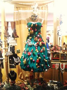Green dress on a mannequin turned into a Christmas tree by adding baubles and tree ornaments #christmasshopwindow