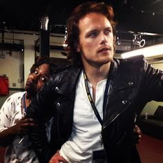 sam heughan back stage--look at that woman's face! LOL! I'd do that same thing.
