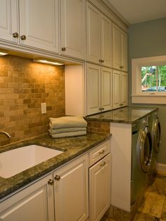 This laundry room is elegantly toned in neutral colors and tile backsplash. The expansive beige cabinetry provides plenty of storage space, while the beautiful stone countertops provide ample workspace.