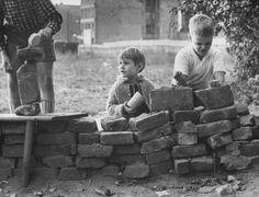 West Berlin children, from left, Peter Friedrich, 5, Katrin Kuhl, 4, and Jurgen Bottcher, 8, build a pretend Berlin Wall in a vacant lot in October 1961.