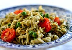 Summer pesto pasta salad with fresh basil pesto, spiral pasta. pine nuts, chopped green onions, peas, and cherry tomatoes.