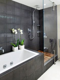 Black tile bath and shower with wooden boards in showers. Would prefer the shower to full be enclosed in glass