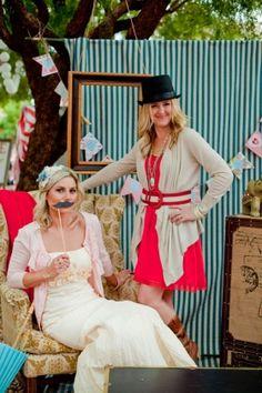 bride and bridesmaid playing dress up at photos booth at circus wedding reception