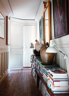 Pour optimiser l'espace et ranger des livres, Jan Couacaud a créé une bibliothèque dans le large couloir, qui sert de présentoir pour exposer fièrement quelques objets authentiques. Deux bancs de pique-nique anglais chinés font office d'étagères pour disposer les nombreux ouvrages.