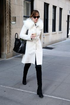 Dakota Johnson wears a winter white Miu Miu coat, skinny black jeans, over-the-knee boots, and an Alexander McQueen tote