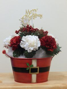 Forget Christmas stockings - this Christmas get a boot! A cute red Santa boot, with a gift box atop it: there are holly leaves and red and gold berries peeking out the top as well. This is a great accent piece; it could be used in a hallway, on a side table, or maybe in a window. The decoration is about 11 inches high, 8 inches wide, and 3 inches deep.