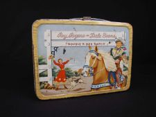 """Roy Rogers and Dale Evans Lunch Box: This metal lunch box was manufactured by Thermos in 1954, and it came with an aluminum thermos. This Roy Rogers and Dale Evans lunch box features an image on front lid of Dale in a red dress, greeting Roy on his horse Trigger at gate of the """"DOUBLE R BAR RANCH"""". The back has a wood grain print with """"RR"""" brand and name for box owner on the back, 2 vent slots."""