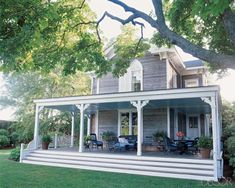 Loving the colors of this wrap around porch and the shape of the windows. The trim is a beautiful detail without being too frilly. I would add fans and a porch swing.