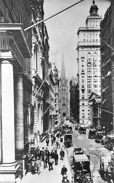 A view looking west on Wall Street about 1890 from the corner of Wall and Broad. Trinity Church is at the end of the street. To the left is the old Assay Office