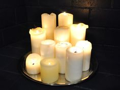 Candles in fireplace on round mirror, mirror reflects light and helpful in catching wax drips