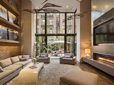 Exposed brick wall, beautiful window with a lot of natural light. I also enjoy the long fireplace! The tv also being not to far from the couch is great too!