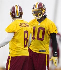 Washington Redskins rookie quarterback Robert Griffin III, right, talks with quarterback Rex Grossman during an organized team activity for the NFL football team on Monday, May 21, 2012 in Ashburn, Va.  (AP Photo/Evan Vucci)