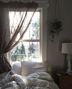 Love the bedding, the hanging plant, and the gauzy curtain.