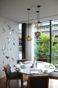 Our Niche Stargazer, Oculo and Solitaire pendants hang gloriously above this dining room table at the luxurious ORU in Vancouver, British Columbia.