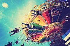 Lovely action shot composition of people on the rainbow colored fairground ride's swings, under the blue and yellow skies that blend into the carnival swing's striped colors. Nice blurriness like the sun in the upper left corner. -DianaDee Osborne.