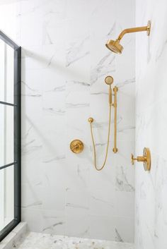 A steel-and-glass enclosure framed a stunning walk-in shower with a brass shower. A steel and glass enclosure frames a stunning walk in shower featuring a brass shower kit mounted to large white marble surround tiles on a wall adjacent to a brass sprayer. Gold Shower, Shower Taps, Shower Fixtures, Black Shower, Shower Enclosure, Kohler Bathroom, Brass Bathroom, Master Bathroom, Master Shower
