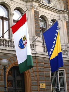 The flag of Bosnia and Herzegovinia (right) and the flag of Federation of Bosnia and Herzegovina (left) in front of the Government of Federation of Bosnia and Herzegovina in downtown Sarajevo.