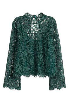 Blusa em renda: Blusa de corte évasé em renda com pequena gola subida, abertura e botão oculto na parte de trás do pescoço e mangas trombeta compridas. Forrada com top interior de jersey cosido à blusa.