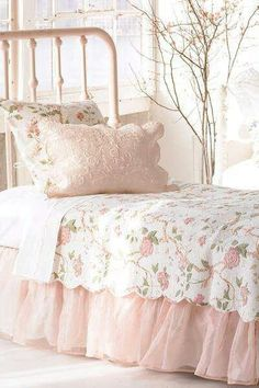 Bedding: Light pink colored pillows and a floral printed bedspread.