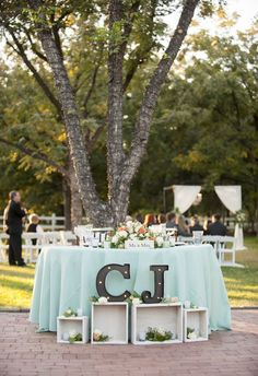 Precious sweetheart table, aqua tablecloth, peach florals, chic letters via Drew Brashler Photography