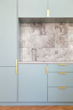MCM light blue kitchen cabinets, gold hardware and marble back splash! Beautiful!