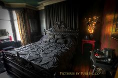 This room is Gothic in style because it uses dark colors for the bed and furniture, it has a grand window, and the bed is huge.