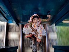 A woman is riding between the railway carriages of a local train heading north from Dhaka, the Bangladesh capital. (This photo and caption were submitted to the 2011 National Geographic Photography Contest.)