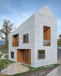 A pitched roof and six walls appear as a single block of concrete around these two residences in Geneva by Swiss architects clavienrossier