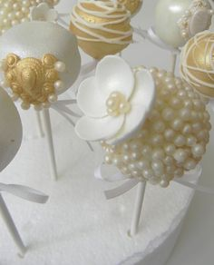 wedding cake pops for the dessert table. I like the gold and white in the back
