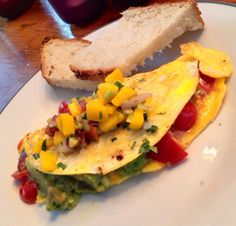 Local farm eggs, home-made guacamole, nitrite-free bacon, jack cheese and tomato omelette; topped with Dana's home-made mango chutney and a few slices of her home-made bread .. sprinkled with fresh cilantro and Halen Môn sea salt.
