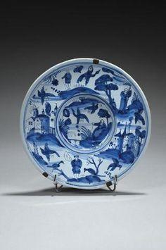 Nevers Plat rond à décor en camaïeu bleu de Chinois et bergers dans un paysage avec fortifications, oiseaux et papillons en vol. XVIIe siècle Diam. : 29 cm