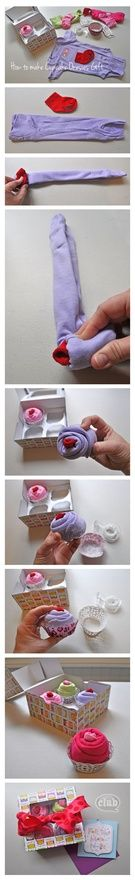cupcake baby gift steps -   Fold each onesies long ways twice in on itself, so it is a very thin long piece.Then take one sock and let the top of the toe area of the sock pop above the onesie.Roll the sock tightly in the middle of the onesie to create the cupcake shape While holding the rolled onesie take a piece of clear scotch tape to secure.