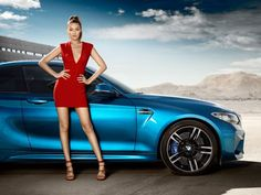 Gigi Hadid models a little red dress while posing next to the BMW M2 Coupé