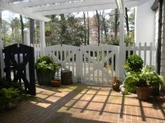 cute area between a garage and house with brick floor and cute white fencing...:)