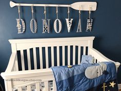 """58"""" 7-Peg Stained or Painted Paddle Name Rack with Seven 9"""" Decorative Letters and Rope Nautical Whale Navy and Gray Nautical Nursery Decor #nautical #baby #babynamesign #nauticaldecor #personalizedbaby #canoepaddle #paddle #oar #oarpegrack #nauticalbaby #hangingletters #hangingbabyname #woodletter"""