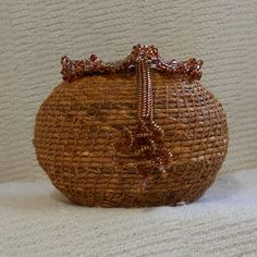 """One continuous length of Siberian iris leaves & waxed linen thread, coil is wound around or on top of itself, in an expanding or decreasing spiral. A """"basket weaver's buttonhole"""" stitch is used to bind the new coil to the previous one."""