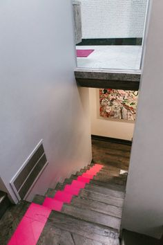 A pink stripe from the ceiling to the bottom of the stairs