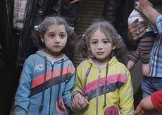 Girls who survived what activists said was a ground-to-ground missile attack by forces of Syria's President Bashar al-Assad, hold hands at Aleppo's Bab al-Hadeed district April 7, 2015. Stringer . / Reuters