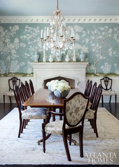 A celadon-hued Gracie wallpaper sets a romantic tone in the dining room, where a Baker buffet, dining table and chairs create a fresh twist on tradition.