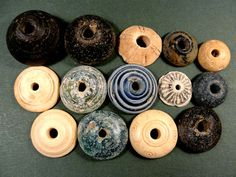 Roman, 100-300 AD.  14 ancient Spindle Whorls.   Faience, bone or ivory, steatite and glass. Largest is 2.5 cm +/-