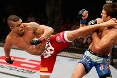 """""""Devastating spinning back kick by Vitor Belfort!"""" """"And its all over"""" """"Vitor knocks out Luke Rockhold!""""...That would be the caption of this photo. Vitor on the left Luke on the right. This was a super mach up between 2 top level mixed martial artiest. Martial arts have been apart of my life for a long time now and there is nothing more exciting then watching to top athletes duke it out."""