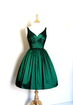 This sophisticated prom dress is made from a dark emerald green taffeta. The plunging neckline at the back and bust gathering make for a classic