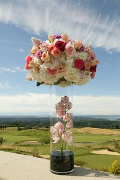 Could do something like this (with different flowers) on top of white columns for ceremony