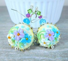 Handmade colorful pastel floral earrings featuring turquoise blue, lilac purple, white, ivory and green floral artisan crafted lampwork beads; sterling silver; blue, green and purple Swarovski crystals.  These gorgeous earrings are composed of beautifully detailed, 20mm lampwork lentil beads created by an SRA lampwork artist. The beads are ivory with aqua blue, purple and white flowers and green leaves. Blue, purple and green Swarovski crystals compliment the beads and add sparkle. Sterling…