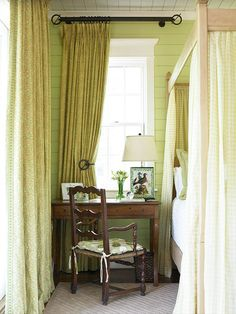 Green walls, green drapes, and green on the bed sheers frame the walnut chair and writing desk. - Traditional Home ®/ Photo: Emily Followill / Design: June Price