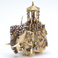 "Gemset-encrusted carved ivory elephant with gilt silver trappings, set with sapphires of varying colors, emeralds, rubies, moonstones, opals, coral, turquoise and star sapphires, ca. 1960. 4 1/2"" x 4""."