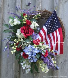 American Flag Garden Splendor Wreath. A lovely collection of classic summertime garden favorites gather together upon a rustic grapevine frame to create this designer masterpiece. An abundance of Hydr