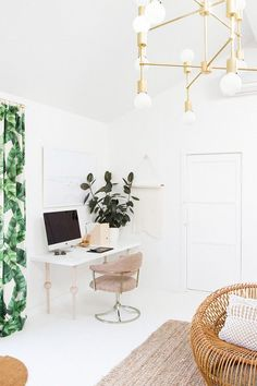 Home office with white walls, a chandelier, a simple IKEA desk, and a pink chair